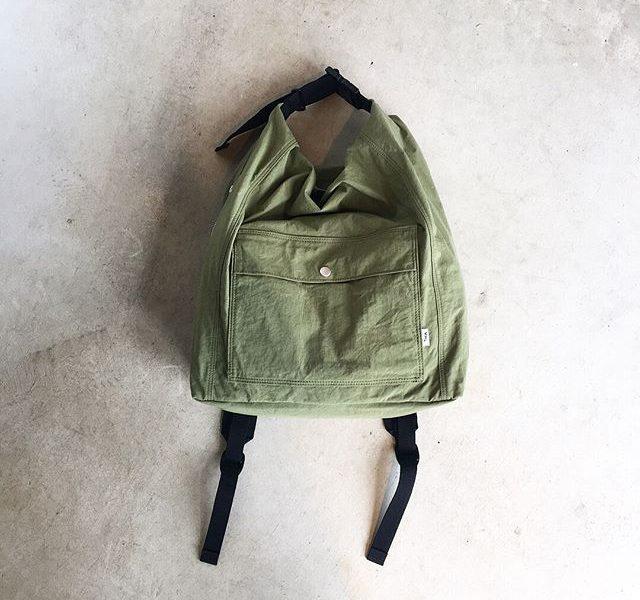 .持った時のクシャッとなった表情が愛らしいMHL.MATT NYLON.ナイロンでありながら天然繊維の天日干しの風合いと膨らみを持った素材感。.color カーキ、ブラック.size W35㎝、H49㎝、D14㎝.#MHL.#MATT NYLON #bag#daypack#hausmatsue #島根#松江