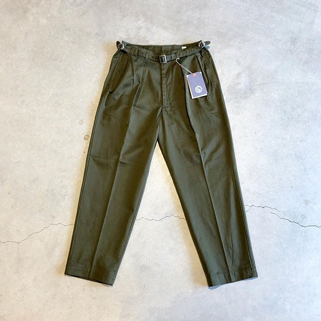 ".○KAPTAIN SUNSHINE / Grukha Trousers.旧イギリス軍のグルカパンツを基に現代的なフィットに再構築した""Groukha Trousers""。腰回りに配されたベルテッドとアジャストバックルによりベルトレスでの着用が可能です。全体的に太めながらも裾に向かって絞り込むテーパードしたシルエット。深いツープリーツも見る人の目を惹き、凛々しく品のあるドレスカジュアルな雰囲気に仕上がっています。.#kaptainsunshine#キャプテンサンシャイン#grukhatrousers#military#madeinjapan"