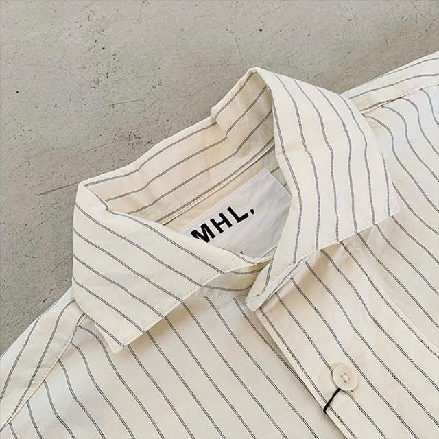 ヴィンテージのワークウエアスモックをベースにデザインされたMHLASMMETRIC COLLARD SHIRTアシンメトリーな衿が個性的なワークシャツです。color ホワイトsize  Ⅰ .ⅡHÅUSのハウエルのインスタはこちらです︎@haus_howell #MHL#TWIN STRIPE COTTON#shirt#ワークシャツ#hausmatsue #島根#松江